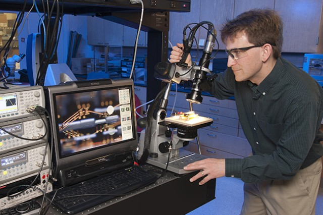 "Dr. Ronald Polcawich performs high-resolution imaging and testing of a millimeter-scale robotic leg structure. The roughly 3-mm-long leg consists of segments of piezoelectric thin-film actuators and thin-film copper sections designed to mimic the kinetics of a leg with a ""hip,"" ""knee"" and ""ankle"" joint sections. These ""legs"" have demonstrated the ability to move, lift (e.g., salt crystal in image), and resist impact into the silicon substrate."