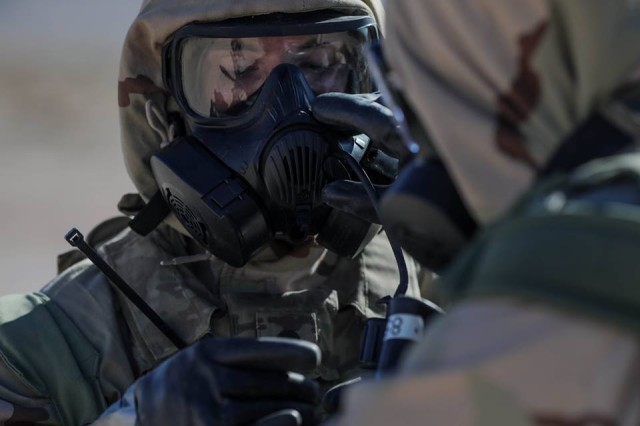 U.S. Army Soldiers assigned to 1st Battalion, 64th Armored Regiment, 1st Brigade Combat Team, 3rd Infantry Division, adjust and utilize their hydration system around the perimeter of a simulated chemically contaminated facility during Decisive Action Rotation 18-01 at the National Training Center in Fort Irwin, California, Oct. 23, 2017. When the unit had to relocate the brigade command post, Soldiers wore this gear, making it even more difficult to set up and wire a large brigade command post. Secure Wi-Fi made it much easier and faster to set up a network under these extreme conditions, and users were able to connect to the network and to their mission command systems earlier and stay connected longer prior to the next command post relocation.
