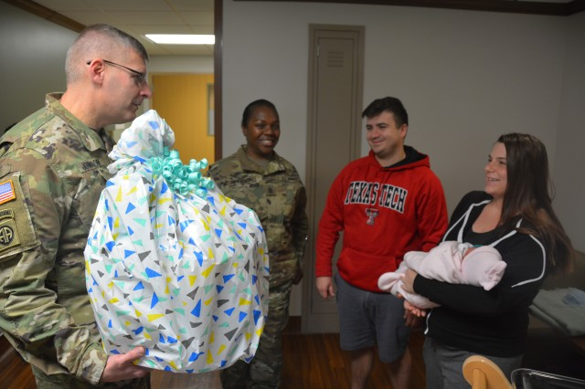 Brooke Army Medical Center commander Brig. Gen. Jeffrey Johnson and Warrior Transition Battalion Command Sgt. Maj. Karen Hinckson deliver a gift basket to Petty Officer First Class Dylan Pendleton, his wife Rachel and baby Violet. Violet was BAMC's first baby in the New Year born Jan. 1, 2018 at 2:27 a.m.