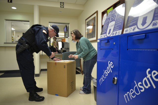 Security officer, Mike Echols, assists Nancy Pimentel, a pharmacy technician at GLWACH, with the management of the Pharmacy's MedSafe prescription disposal service for unused or unwanted prescription medications.