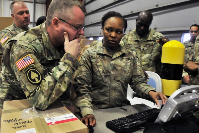 Pfc. Marissia Williams (right), of the 543rd Composite Supply Company's supply support activity, coaches Brig. Gen. Chris Mohan, commanding general of the 3rd Expeditionary Sustainment Command, on inventory receiving procedures. Through Williams' demonstration, Mohan discovered ways larger Army systems were impeding efficiency at the lower levels.