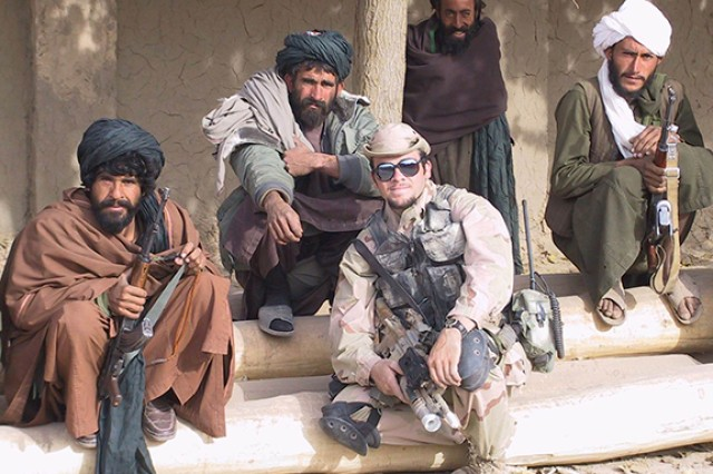 Now-Chief Warrant Officer 2 Brad Fowers poses with Afghan fighters and warlords who opposed the Taliban. Fowers served on one of the first Special Forces detachments from the U.S. Army Special Operations Command's 5th Special Forces Group (Airborne) to arrive in Afghanistan following Sept. 11, 2001. Their mission was to destroy the Taliban regime and deny Al-Qaida sanctuary in Afghanistan. They scouted bomb targets and teamed with local resistance groups.