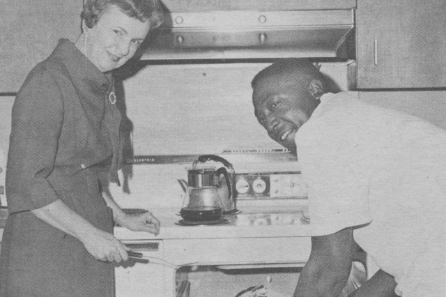 Mrs. Shelton E. Lollis beaming while Sp/6 Carl Smith removes a turkey from the oven.  She is the wife of ATAC's Commanding General.