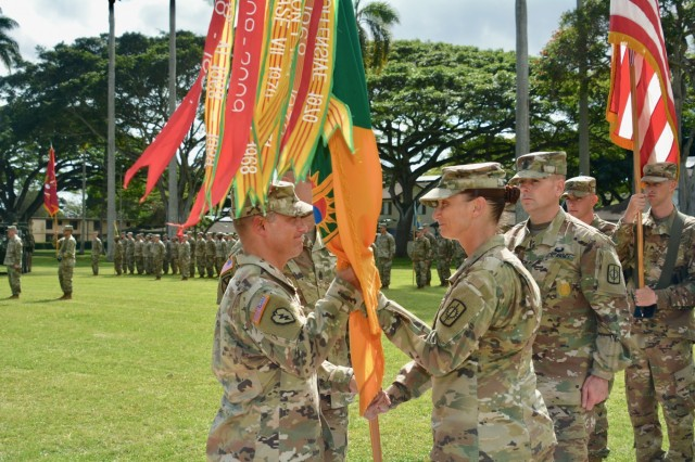 Command Sgt. Maj. Teresa Duncan passes the 8th Military Police Brigade Colors to the brigade commander, Col. Shannon-Mikel Lucas, during a Change of Responsibility ceremony January 9 on Schofield Barracks' Hamilton Field. (U.S. Army Photo by Sgt. 1st Class John Brown, 8th Military Police Brigade Chief of Public Affairs)