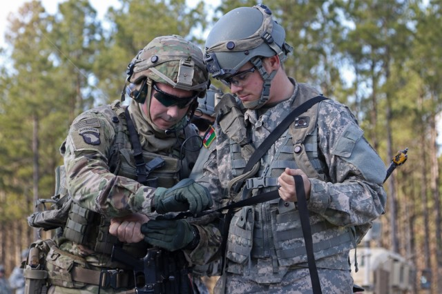 A Soldier from 2nd Battalion, 1st Security Force Assistance Brigade, helps an Afghan National Army role player apply a tourniquet during a simulated scenario at the Joint Readiness Training Center at Fort Polk, La., Jan. 15, 2018. The JRTC rotation was conducted in order to prepare the newly formed 1st SFAB for an upcoming deployment to Afghanistan in the spring of 2018. SFABs provide combat advising capability while enabling brigade combat teams to prepare for decisive action, improving readiness of the Army and its partners. (U.S. Army photo by Pfc. Zoe Garbarino/Released)