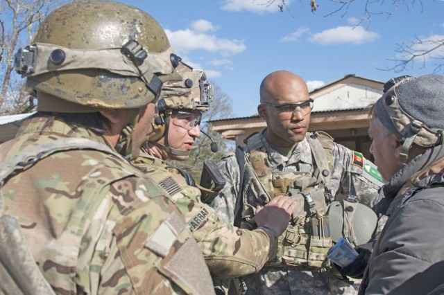 Capt. Kristopher Farrar, an infantryman assigned to 1st Battalion, 1st Security Force Assistance Brigade, center left, communicates to an acting village elder that the Afghan National Army, is ready to provide security for the village during a Joint Readiness Training Center rotation, Jan. 15, 2018, at Fort Polk, La. The 1st SFAB is a new formation specially trained and built to enable combatant commanders to accomplish theater security objectives by training, advising, assisting, accompanying, and enabling allied and partnered indigenous security forces. (U.S. Army photo by Sgt. Arjenis Nunez/Released)