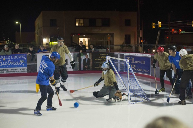 A Montgomery County player moves in for a shot against a 101st Airborne Division (Air Assault) player during the first-ever broomball competition at the Downtown Commons ice rink in Clarksville, Tennessee, Jan. 10, 2018. The game came about after Jim Durrett, Montgomery County mayor, issued a challenge to Maj. Gen. Andrew Poppas, 101st Airborne Division (Air Assault) commander. Although a close match that went into sudden-death overtime, Poppas and his team came away victorious with a 2-1 win. (U.S. Army photo by Sgt. Samantha Stoffregen, 101st Airborne Division (Air Assault) Public Affairs)