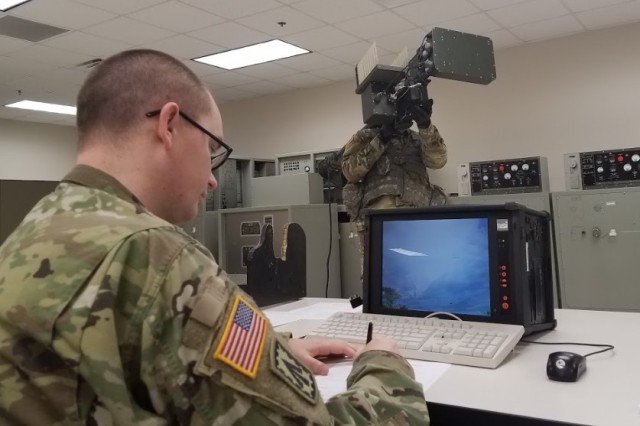 An 82nd Airborne Division Soldier (standing) undergoes a virtual reality FM-92 Stinger evaluation while being evaluated by Staff Sgt. Jeremy Capps, a short range air defense instructor.