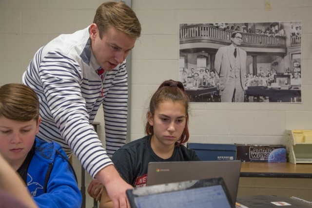 "Gregory Kessler, an English language arts teacher at Horace Mann Middle School in Franklin, Mass., helps a student organize an argumentative essay about Harper Lee's novel ""To Kill a Mockingbird"" Jan. 12, 2018. In addition to being a full-time teacher, Kessler is also a Public Affairs Officer with the 65th Press Camp Headquarters, Massachusetts Army National Guard."