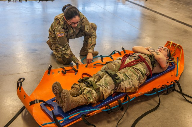 Sgt. Marbella Allan positions and fastens Staff Sgt. Sasha Gonzalez into a stretcher during testing on patient packaging at the end of the first week of the USACBRNS' Technical Escort Course.