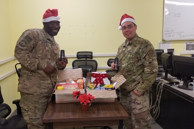 Staff Sgt. Adebowale Goyea and Maj. Daniel Howser inspect their holiday care packages sent to them in Afghanistan. Goyea and Howser are part of a team of Soldiers spending the holidays deployed to support Operation Resolute Support in Afghanistan. Goyea is a contract specialist with MICC-Fort Bragg. Howser is the team lead for the 614th CT. UA-58345956-1  (Courtesy Photo)