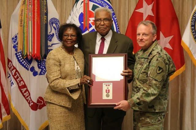 The Superior Civilian Service Award is presented to the Aviation and Missile Command's Resource Management deputy director Mark Barkley upon his retirement after a 57-year career as a government employee. With Barkley is his wife, Arrie Ann. Presenting the award is AMCOM commander Maj. Gen. Doug Gabram.