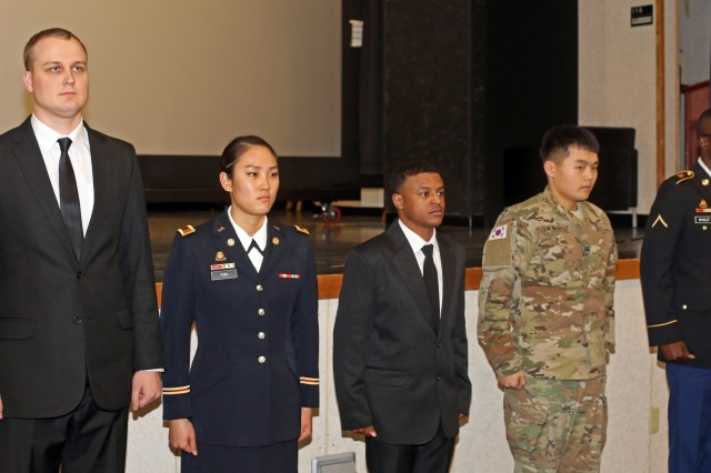 Soldiers from various Area IV units receive coins for excellence for their participation in the Area IV Martin Luther King Jr. observance ceremony, Jan. 11 at the Camp Henry post theater, Daegu, Korea.The Soldiers from left to right are 2nd Lt. Joshua Mayer of Lincoln, Nebraska, 2nd Lt. Sherry Kim of Cherry Hill, New Jersey, Sgt. Ike Mathes of Detroit Michigan, Cpl. Um Yong Chul of Seoul, Korea and Pvt. Ezekiel Whaley of Norfolk, Virginia.