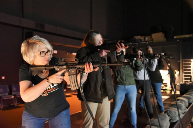 (Left) Tawny Jimeno and other students from U.S. Army Garrison Rheinland-Pfalz Middle Management Development Program use the Engagement Skills Trainer in Baumholder, Germany. The EST uses realistic simulations and model weapons, requiring participants to make instant life-or-death decisions relying heavily on knowledge, teamwork and communication.