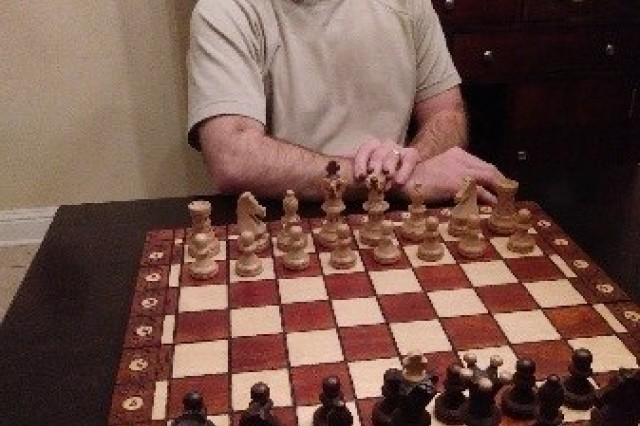 Retired Staff Sgt. Patrick Barrington sits at a chess board planning his first move.