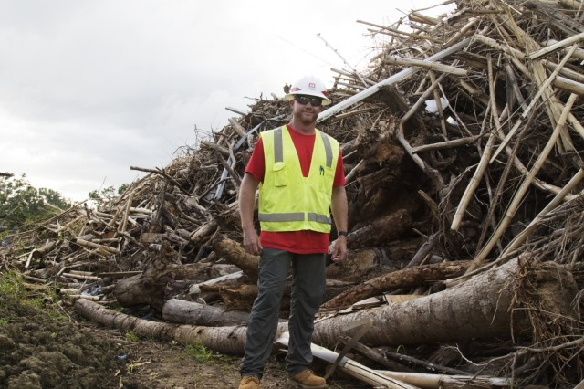 Seth Finn, a U.S. Army Corps of Engineers Quality Assurance specialist from the USACE Louisville District, stands near a pile of vegetative debris at the Office for the Improvement of Public Schools of Puerto Rico (OMEP) in Bayamón, Puerto Rico Jan. 17. The OMEP site is one of seven educational facilities where USACE began clearing debris from Hurricane Maria the week of Jan. 14, in coordination with the Federal Emergency Management Agency and local governments.
