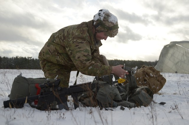 A U.S. Army Paratrooper assigned to 4th Battalion, 319th Airborne Field Artillery Regiment, 173rd Airborne Brigade, gathers his equipment after safely landing from an airborne operation at the 7th Army Training Command's Grafenwoehr Training Area, Germany, January 17, 2018. (U.S. Army photo by Christoph Koppers)