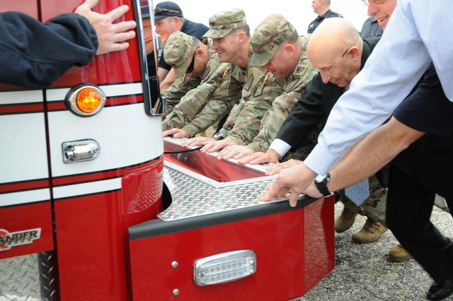 Col. Brian E. Walsh, Fort Rucker garrison commander, William G. Kidd, USAACE and Fort Rucker deputy to the commanding general, Command Sgt. Major. Christopher D. Spivey, Fort Rucker garrison command sergeant major, and Sgt. Maj. Andrew D. Shaw, Directorate of Public Safety sergeant major, along with firefighters and DPW officials, help push the new fire engine into the apparatus bay of the new fire station at Knox Army Heliport Jan. 10.