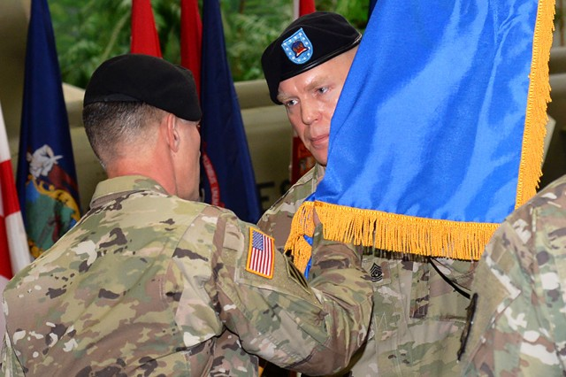 Command Sgt. Maj. George S. Webster, ATSCOM command sergeant major, assumes responsibility as the unit colors pass from Command Sgt. Maj. James R. Schley, outgoing command sergeant major, to Col. Michael E. Demirjian, ATSCOM commander, to Webster during a ceremony at the U.S. Army Aviation Museum Jan. 9.