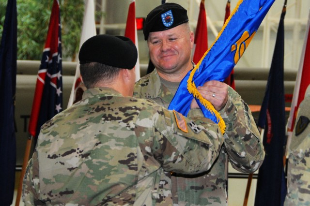 Sgt. Maj. Jerry M. Cowart Jr., ACLC sergeant major, accepts the unit colors from Col. Michael J. Best, ACLC commander, as he assumes responsibility from Sgt. Maj. Antonio R. Lopez during a ceremony at the U.S. Army Aviation Museum Jan. 11.