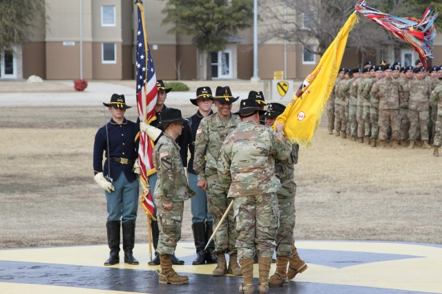 Outgoing Commander Lt. Col. Brian McCarthy passes the guidon to Greywolf Commander John K. Woodward officially relinquishing command of 3rd Battalion, 8th Cavalry Regiment, 3rd Armored Brigade Combat Team, 1st Cavalry Division, during the change of command ceremony, on Cooper Field, Jan. 11.