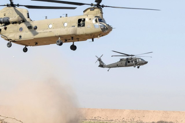 A UH-60M Black Hawk helicopter, right, and a CH-47 Chinook helicopter, both from the 2nd General Support Aviation Battalion, 149th Aviation Regiment Task Force Rough Riders, land in August before inserting paratroopers from 2nd Brigade Combat Team, 82nd Airborne Division, during an aerial response force exercise at Camp Taji Military Complex in Iraq. It is in the government's best interest to develop an aviation mission systems architecture that will encourage shared capabilities.