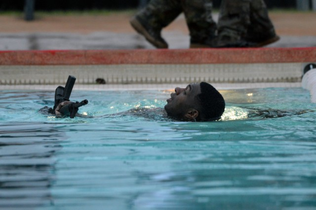 "A Soldier assigned to Headquarters and Headquarters Company, 3rd Brigade Combat Team, ""Broncos,"" 25th Infantry Division, performs the 25-meter surface swim with a rubber M4 carbine portion of the Combat Water Survival Test at Richardson Pool on Schofield Barracks, Hawaii, Jan. 19, 2018. The purpose of CWST is to assess a Soldier's water survival abilities and build confidence. (U.S. Army photo by Staff Sgt. Armando R. Limon, 3rd Brigade Combat Team, 25th Infantry Division)"
