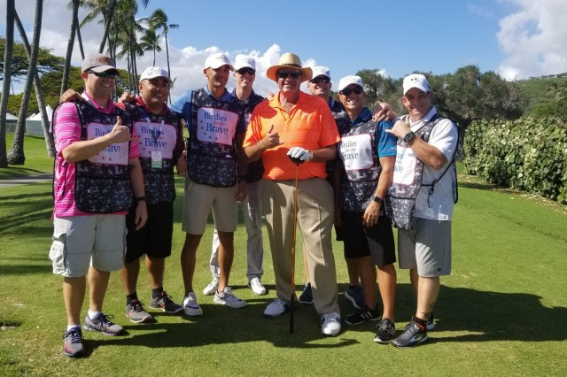 Chris Berman, former ESPN spokesperson, poses for a Birdies for the Brave photo with service members on the 18th hole fairway, during the Sony Open.  Birdies for the Brave is a national military outreach initiative dedicated to honoring and showing appreciation to the courageous men and women of the United States Armed Forces and their families.  (U.S. Army Photo by Staff Sgt. John Portela)