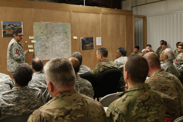A role player member of the Afghan National Army briefs fellow leaders about an upcoming mission while key leaders of the 1st Security Force Assistance Brigade listen through an interpreter during a command post exercise held Jan. 15, 2018, during the first-ever, month-long 1st SFAB training rotation at the Joint Readiness Training Center in Fort Polk, La. The CPX was specifically geared towards preparing the 1st SFAB staff for roles they may encounter during their upcoming deployment to provide training and advising assistance to Afghan National Security Forces. (U.S. Army photo by Spc. Noelle E. Wiehe, 50th Public Affairs Detachment/ Released)