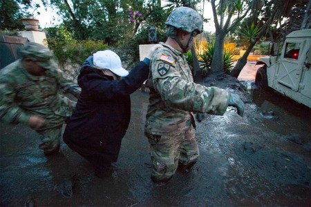 Sgt. Jose Paiz, right, and Staff Sgt. Michael Aguilar, left, both of the 1114th Composite Truck Company, California National Guard, guide a woman through thick knee-deep mud, Jan. 12, 2018, from a Montecito, Calif., home to the Soldiers' Humvee. The 1114th is credited with rescuing or evacuating more than 1,800 people in the Montecito area following a deadly mudslide that struck the city in the predawn hours, Jan. 9.
