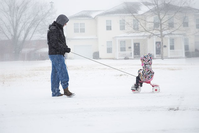 Staff Sergeant Michael Hough, 39th Brigade Engineer Battalion, 2nd Brigade Combat Team, 101st Airborne Division, pulls his 4-year-old daughter Sophie on her tricycle during the snow storm Friday in Zahn Park. Fort Campbell received about 6.5 inches of snow from back-to-back storms.