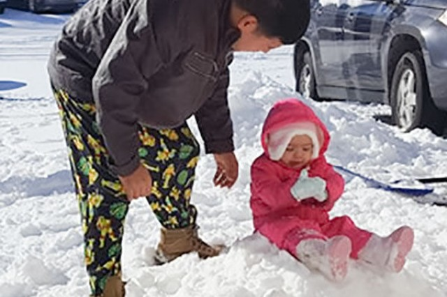 Sergeant Leonardo Gonzalez, 3rd Battalion, 320th Field Artillery Regiment, 101st Airborne Division Artillery Brigade, 101st Abn. Div., plays with his youngest daughter, Serena, 15 months old, outside their Pierce Village home, following a recent snow storm.