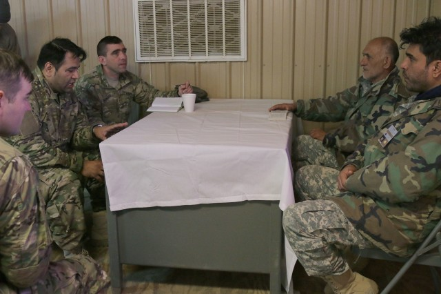 Maj. Jason Moncuse, Company C commander, 1st Security Force Assistance Brigade, speaks with role playing Afghan National Army leaders through his interpreter as his team begins planning for the next day's mission during the 1st SFAB's first-ever Joint Readiness Training Center rotation at Fort Polk, La, Jan. 18, 2018. The 1st SFAB is training at JRTC for their upcoming spring 2018 deployment to provide training and advising Afghan National Security Forces. (U.S. Army photo by Spc. Noelle E. Wiehe, 50th Public Affairs Detachment, 3rd Infantry Division/ Released)