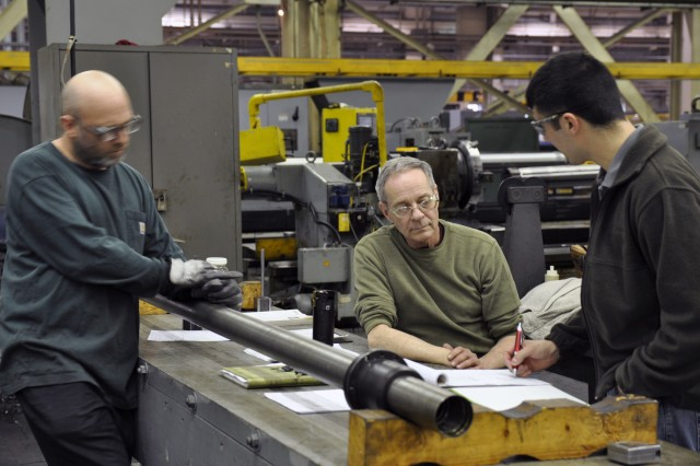Skilled labor is hard to fine and so, the Arsenal takes every opportunity to mentor its current labor force.  Here, senior machinist Peter Northup, center, is discussion mortar production with Machine Tool Inspector Dwight Collin, left, and former apprentice Stephen Pawlik.
