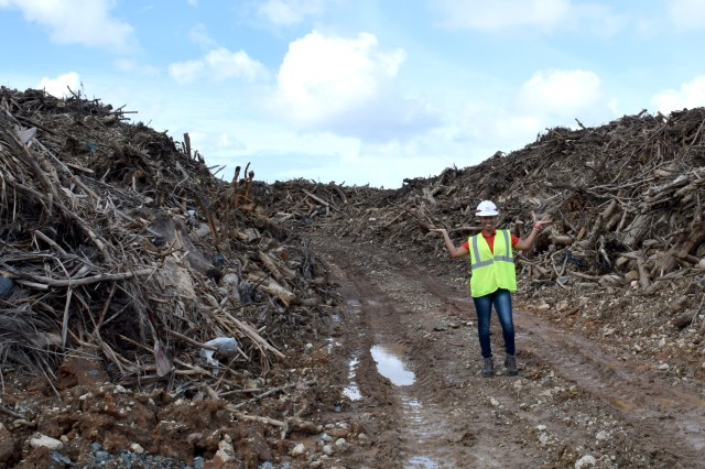 U.S. Army Corps of Engineers Debris Mission Manager Jasmine Smith stands among the mountain of vegetative debris that has been collected at one of 33 sites across Puerto Rico in support of Hurricane Maria recovery efforts.