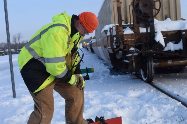 Crane Army rail workers remove ice from rail switches during subfreezing temperatures. Any amount of ice present on these switches can derail trains, injuring employees and preventing munitions from reaching Warfighters.