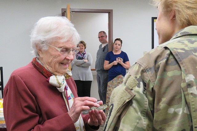 Ruth Knasel admires a coin given to thank her for 34 years of service as a Red Cross volunteer in Madigan Army Medical Center's family medicine clinics by Maj. Angelika Chiri, chief nurse of the Primary Care Service Line, at a party to celebrate Knasel's 95th birthday, Jan. 5 on Joint Base Lewis-McChord, Wash.