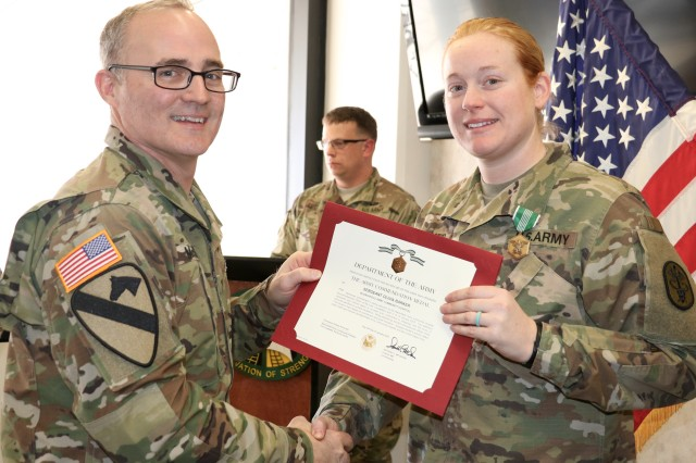 FORT CAMPBELL, Kentucky —  Blanchfield Army Community Hospital Commander, Col. Anthony L. McQueen, presents Sgt. Olivia Barker the Army Commendation Medal during an award ceremony Jan. 19, for her selection as the hospital's NCO of the Year. Barker and fellow candidates competed in nine events including marksmanship, a physical fitness test, written exam with essay, selection board appearance, land navigation and battle drills. The winners will go on to compete in the Regional Health Command-Atlantic Best Warrior Competition later this year. U.S. Army photo by Maria Yager.