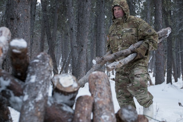 U.S. Army Alaska Commanding General Maj. Gen. Mark O'Neil gathers logs to construct a thermal shelter during the Northern Warfare Training Center's Cold Weather Orientation Course November 29, 2017 at Black Rapids Training Site, Alaska. Members of the 297th Infantry Regiment, Alaska Army National Guard recently completed similar cold-weather training in January 2018.