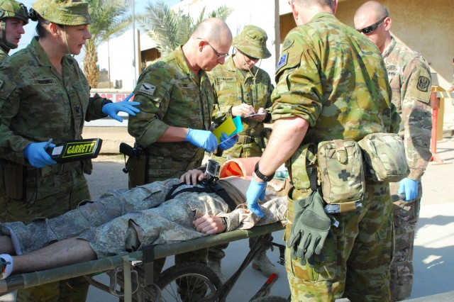 Soldiers assigned to the 449th Combat Aviation Brigade and medical personnel assigned to the Australian army work together to assess a patient's initial injuries after a simulated gas bottle explosion during a mass casualty training exercise at Camp Taji, Iraq, Jan. 18, 2018.  This training is part of the overall Combined Joint Task Force - Operation Inherent Resolve building partner capacity mission, which focuses on training and improving the capability of partnered forces fighting ISIS.