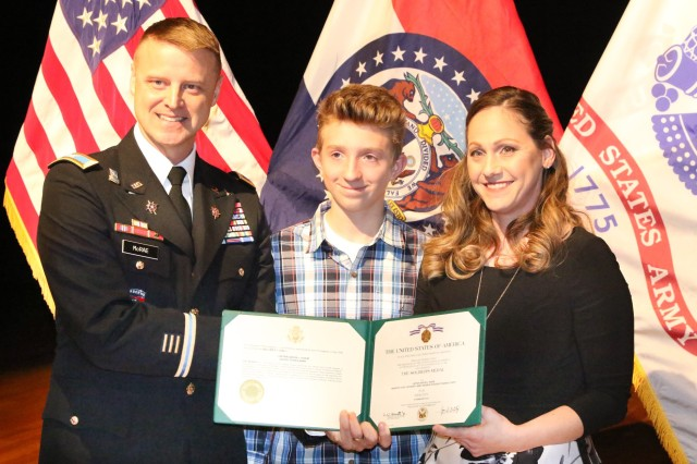 Col. Kenneth McRae, 3rd Brigade commander, presents the Soldier's Medal to Amber Eidem and her son, Skyler, during a ceremony at Missouri State University Jan. 18. Eidem's husband, Capt. Aaron Eidem, was killed in an accident while trying to help a stranded motorist in 2016.