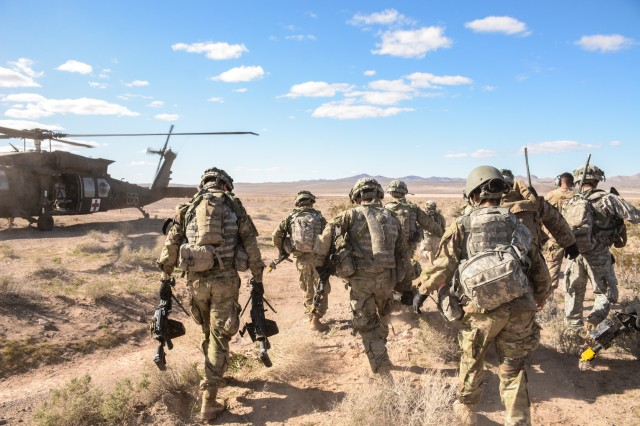 U.S. Soldiers with the 11th Armored Cavalry Regiment evacuate a role playing Soldier in a UH-60 Black Hawk helicopter from a simulated combat zone after securing a helicopter landing zone during their air assault raid during National Training Center 17-04 at Fort Irwin, Calif., Feb. 28, 2017. (U.S. Army photo by Pvt. Austin Anyzeski)