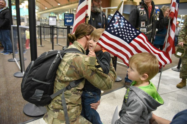 U.S. Army Spc. Kallie Kappes, of the 136th Combat Sustainment Support Battalion (CSSB), North Dakota Army National Guard, kneels to hug her sons as they greet her upon her return from a 10-month deployment to Afghanistan at Hector International Airport, Fargo, N.D., Nov. 16, 2017. (U.S. Air National Guard Photo by Senior Master Sgt. David H. Lipp)