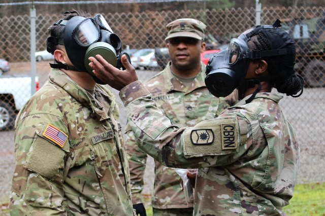 Sgt. 1st Class Yuolanda Carey, of the 773rd Civil Support Team, right, helps Spc. Andrew A. Bonilla, of the 39th Transportation Battalion, make sure his protective mask is sealed Tuesday, January 22 at Breitenwald Training Area near Landstuhl, Germany as Staff Sgt. Patrick McNeely, center, looks on. The active-duty 39th Transportation Battalion trained on Chemical, Biological, Nuclear and Radiological hazards with the Army Reserve's 773rd Civil Support Team.