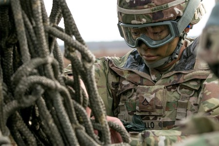 An automated logistics specialist with 1st Infantry Division, inspects a rope harness while preparing equipment to be sling loaded from a helicopter at Skwierzyna, Poland, Jan. 4, 2017. Sling loading is a method of rapidly transporting equipment that is tethered to the bottom of a helicopter with a rope.