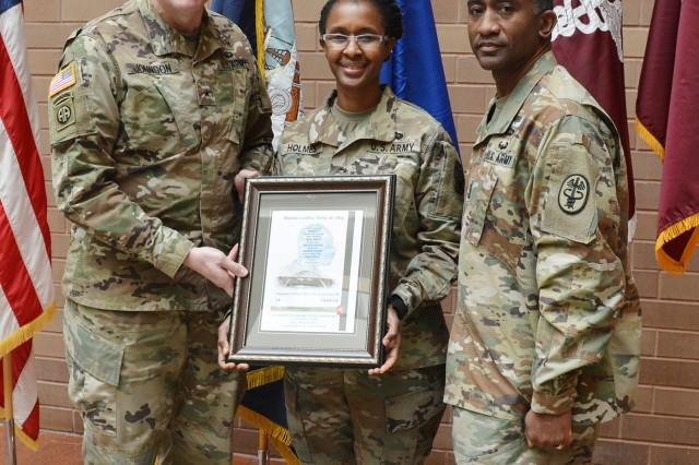 Brig. Gen. Jeffrey Johnson, Brooke Army Medical Center commanding general, and BAMC Command Sgt. Maj. Diamond Hough present Army Col. Valerie Holmes a token of appreciation Jan. 17, 2018 for her role as guest speaker during the Dr. Martin Luther King Jr. observance at BAMC.