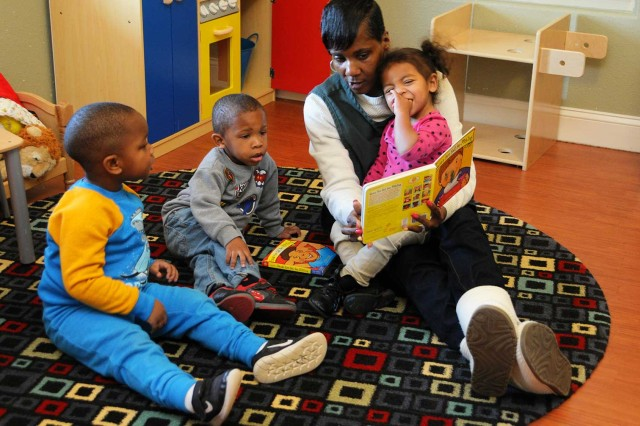 Sonya Hollis, child and youth program assistant, reads a story to Gunnar Nembhard, Zaderian Landrum and Ava Bapp at the Mini CDC Jan. 18.