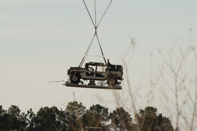 The M-1097 modification Low Velocity Airdrop and Sling Load just above the trees on at Sicily Drop Zone at Fort Bragg, North Carolina. The M-1097 Modification when installed consists of a light-weight roll cage, a weapons station turret, cargo area side boards, and four additional rear seats with restraints.