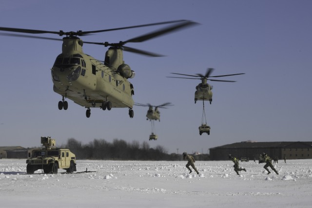 A U.S. Army aircrew assigned to Company B, 6th General Support Aviation Battalion, 101st Combat Aviation Brigade, 101st Airborne Division (Air Assault) position a CH-47 Chinook helicopter above an M1151 high mobility multipurpose wheeled vehicle as 3rd Brigade Combat Team, 101st Abn. Div. Soldiers prepare for sling load operations, Jan. 19, at Fort Campbell. The Soldiers took part in a combined air assault mission to demonstrate and practice their unique capabilities as the world's only air assault division.