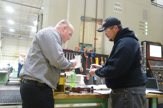Jacob Phillips, Rock Island Arsenal Joint Manufacturing and Technology Center quality assurance specialist, reviews RIA-JMTC machinist Kenneth Pennock's gages in preparation for the quality audit review for ISO 9001:2015 certification.